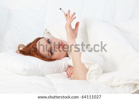 smoking beautiful young woman relaxing in white bedding