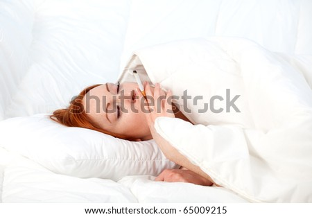 smoking beautiful young woman relaxing in white bedding