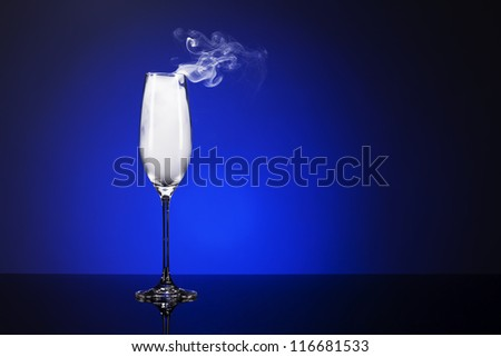 smoking champagne glass on a mirror with blue background light