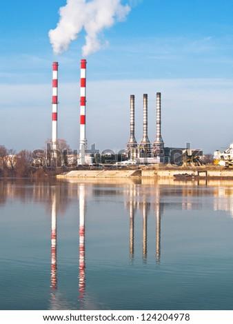 Smoking chimneys pollution air near water, Belgrade Serbia, river Sava - stock photo