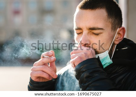 Smoking. Closeup man with mask during COVID-19 pandemic coughing and smoking a cigarette at the street. Smoking causes lung cancer and other diseases. The dangers of smoking. Coronavirus.