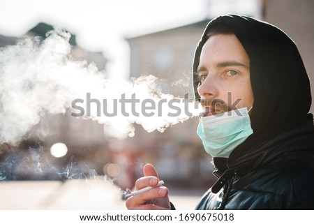 Smoking. Closeup man with mask during COVID-19 pandemic smoking a cigarette at the street. Smoking causes lung cancer and other diseases. The dangers and harm of smoking. Coronavirus.