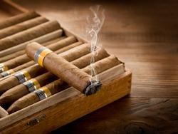 smoking cuban cigar over box  on wood background