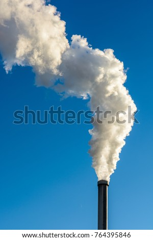Smoking factory chimney. A long cloud of white smoke escaping from a metallic chimney against a deep blue sky.