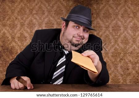 Smoking gangster holding brown envelope, close up.