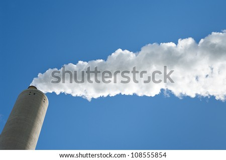 smoking industrial chimney against a blue sky