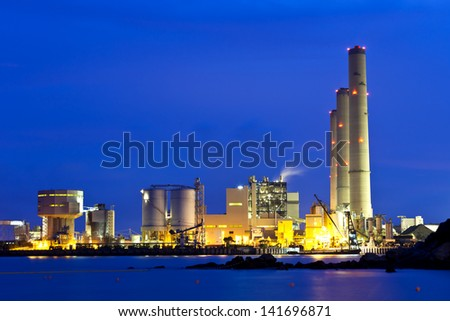 Smoking industrial power plant at night