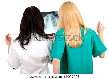 smoking lady doctors in uniforms looking at x-ray, chest, lungs