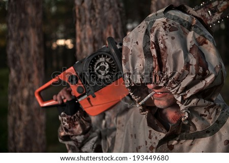 Smoking maniac with the chainsaw dressed in a dirty bloody raincoat. Focus on eyes and cigarette.