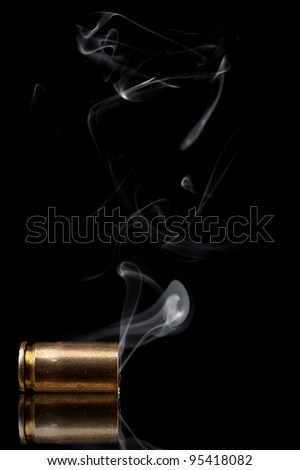 Smoking 9mm bullet casing over black background