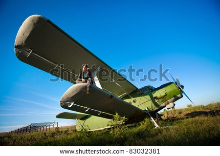 Smoking pilot in the helmet is sitting on the wing of a vintage plane.