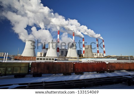 Smoking pipes of power plant against the blue sky - stock photo