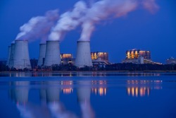 Smoking pipes of thermal power plant on a full moon night