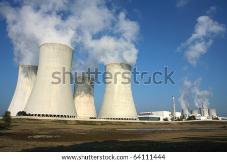 smoking power plant in agriculture field under blue sky