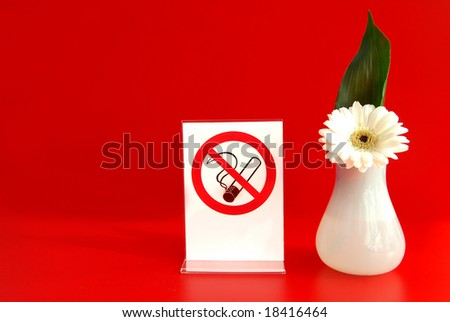 Smoking prohibited sign and decorative flower in no-smoking area on red background