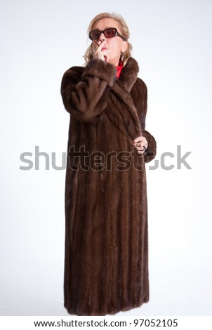 Smoking Senior lady wearing  a mink coat and sunglasses