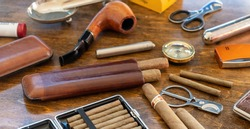 Smoking set accessories. Cigars, pipe, cigarillos and cigarettes, cutters, lighters, cases on a wooden table background. Cuban quality brand cigars, luxury lifestyle closeup view