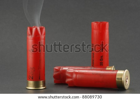 smoking shotgun cartridges on a grey background