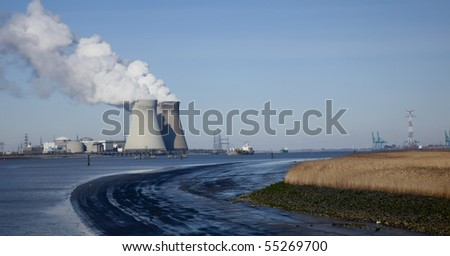 Smoking silos of the nuclear power plant near Antwerp, with boats floating by on the river