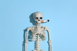 Smoking skeleton with a cigarette in the mouth against a bright blue background. Smoking kills
