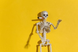 Smoking skeleton with a cigarette in the mouth against a bright yellow background. Smoking kills