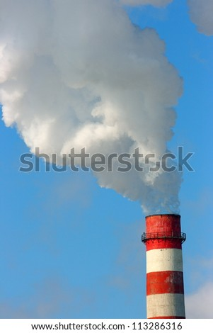 Smoking stack of the thermal power station against a blue sky