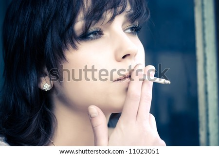 Smoking woman. Portrait in soft yellow and blue tint.