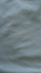 smoky gray material with short pile as a monochrome textured fabric background full frame with slight subtle folds on a fleecy surface, monochrome dark textile for making sportswear