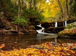 Smoky mountains waterfalls, three separate waterfall in the same shot, autumn leaves in the foreground and distant fall colors in the trees with a carpet of autumn leaves in the foreground