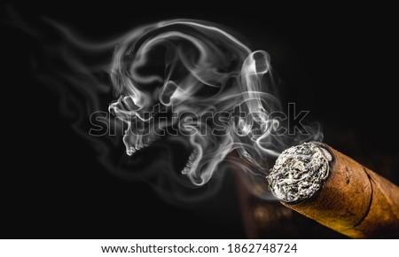 Photo of  smoky skull, macabre smoke cloud with cigarette. Conceptual image anti smoking, smoking kills.