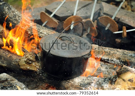 Smoky tourist kettle on fire background and grilled bread