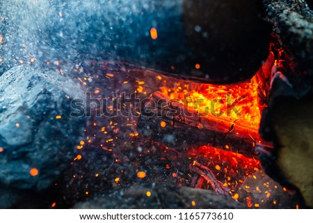Smoldered logs burned in vivid fire close up. Atmospheric background with flame of campfire. Unimaginable detailed image of bonfire from inside with copy space. Whirlwind of smoke and glowing embers. #1165773610