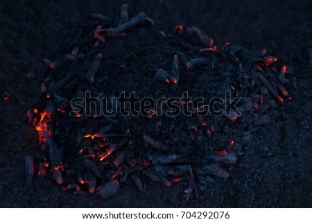 Smoldering ashes of a bonfire. Incandescent orange and red embers texture. Dark background. 商業照片 ©