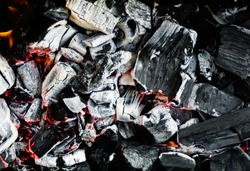 Smoldering embers of fire, live coals, burning charcoal in the background texture, closeup, glowing coal