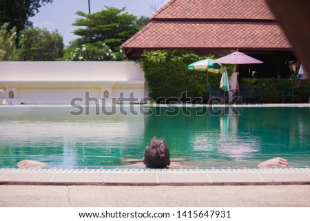 Smooth and Blurred images,Asian male are relaxing by the pool to escape the hot summer of Thailand and are happy to relax during the holidays. Relaxation concept in summer #1415647931
