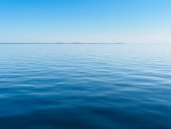 Smooth blue water of the sea with an island in the distance. The White Sea, Russia.
