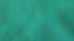 smooth cotton background of a calm mint color with a light texture of small dents, lines and smooth depressions, empty plain greenish textile canvas as a basis for ideas and design