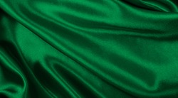 Smooth elegant green silk or satin luxury cloth texture can use as abstract background. Luxurious background design