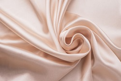 Smooth elegant wrinkled silk fabric background. Abstract crumpled satin texture. Cream color. Soft wavy pastel material, pink glossy textile. Folded cloth, wallpaper.