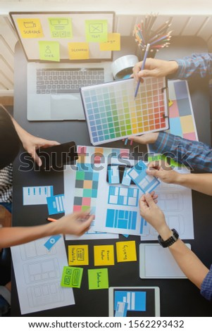 Smooth Focus,A group of web designers are working together to develop a mobile responsive website with UI / UX Front End Designer Previewing. Website development concept UI / UX front end designer.