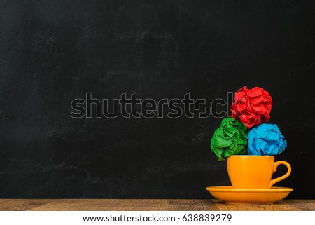 smooth glossy ceramic orange coffee cup put on the wooden surface table with color paper balls stacked together showing blackboard background. #638839279