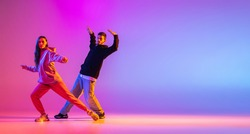 Smooth movements. Two young people, guy and girl, dancing contemporary dance over pink background in neon light. Modern dance aesthetics concept