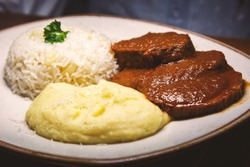 Smooth roast meat, seasoned in its own juice accompanied with mashed yellow potatoes and white rice.