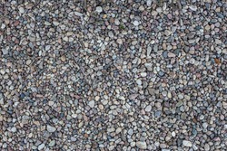 Smooth round pebbles texture background. Pebble sea beach close-up, dark wet pebble and gray dry pebble