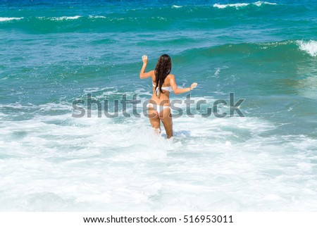Smooth skin tanned slender body woman in white bikini from back. Happy stress free woman walking into the ocean water breathing fresh air enjoying summer vacation. Travel, vacation, freedom, concept. #516953011