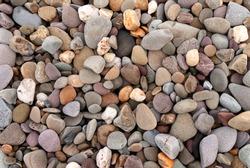 Smooth stones texture background. Rounded stones on Atlantic ocean coast.