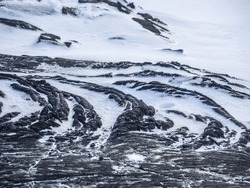 Smooth, undulating surface of black frozen lava covered by snow. Frozen lava wrinkled in folds and rolls resembling twisted rope on Tolbachik volcano area, Kamchatka, Russia. Selected focus.