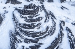 Smooth, undulating surface of black frozen lava covered by white snow. Frozen lava wrinkled in tapestry-like folds and rolls resembling twisted rope on Tolbachik volcano area, Kamchatka, Russia
