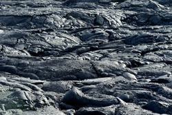 Smooth, undulating surface of frozen pahoehoe lava. Frozen lava wrinkled in tapestry-like folds and rolls resembling twisted rope on Big Island of Hawaii, USA.