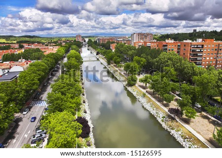 Smooth water of the channel crossing Madrid, trees and cars on quay